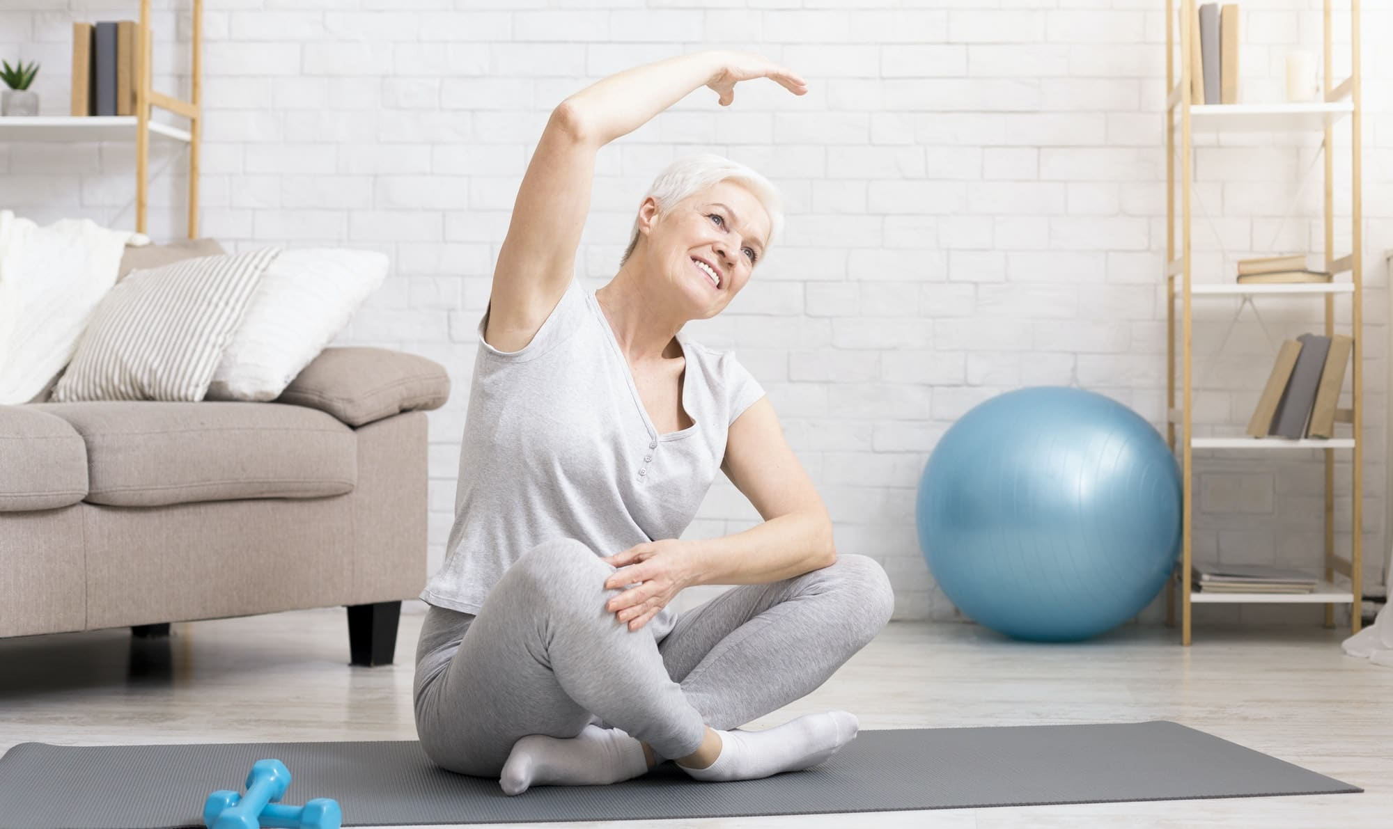 Active senior woman doing exercises at home